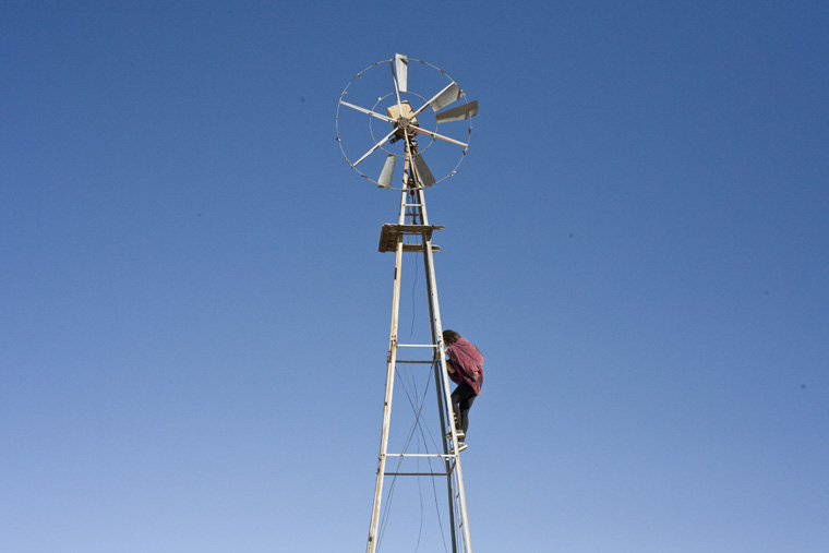 alex climbing windmill against blue sky